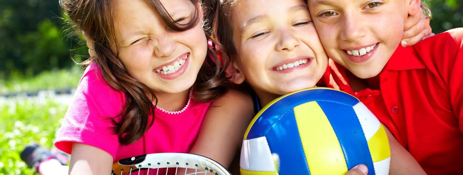 Three children with sports equipment embracing, looking at camera and smiling